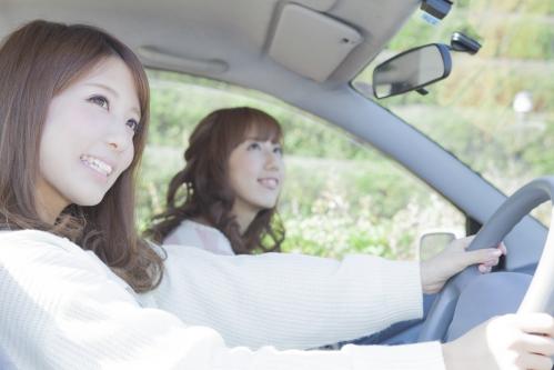 友達とドライブする笑顔の女性
